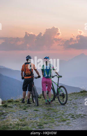 Rear view of young couple of mountain bikers standing in the alpine landscape and looking at view during sunset, - Stock Photo