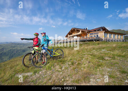 Young couple of mountain bikers standing in alpine landscape and looking at view, Zillertal, Tyrol, Austria - Stock Photo