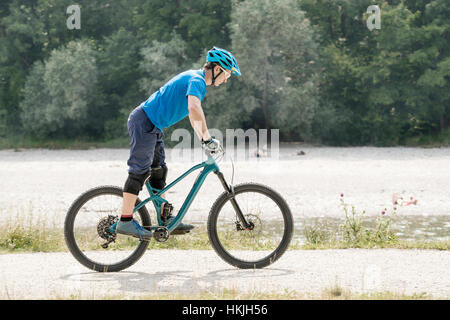 Man riding with mountain bicycle while standing on pedals along river, Bavaria, Germany - Stock Photo