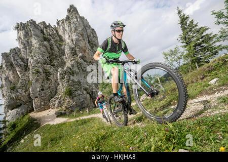Mountain bikers cycling uphill in nature, Kampenwand, Bavaria, Germany - Stock Photo