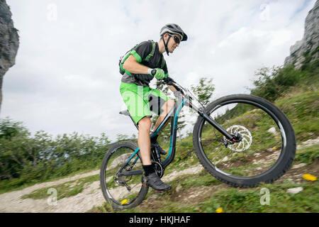 Mountain biker riding on uphill, Kampenwand, Bavaria, Germany - Stock Photo
