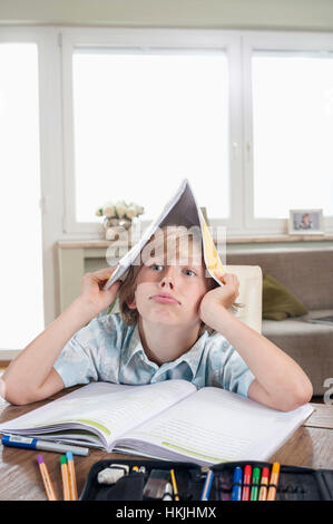 Bored boy with open book on head,Bavaria,Germany