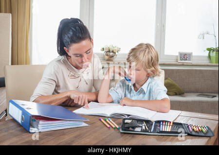 Woman helping her son with his homework,Bavaria,Germany - Stock Photo