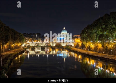 Illuminated St. Peter's Basilica by bridge over river at night, Rome, Italy - Stock Photo