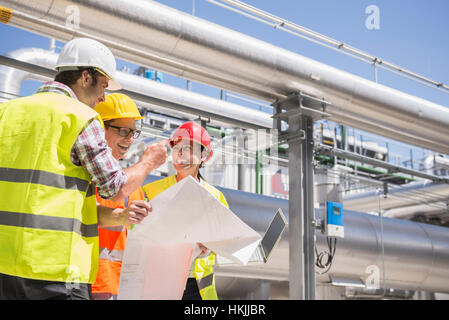 Engineer and workers in meeting on the area of a geothermal power station, Bavaria, Germany - Stock Photo