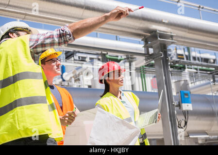 Engineer and workers in meeting on the area of a geothermal energy power station, Bavaria, Germany - Stock Photo