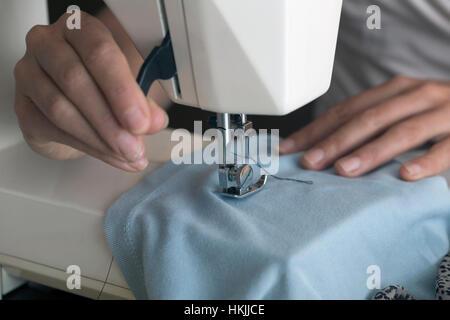 Female dressmaker stitching cloth on sewing machine, Freiburg im Breisgau, Baden-Württemberg, Germany - Stock Photo