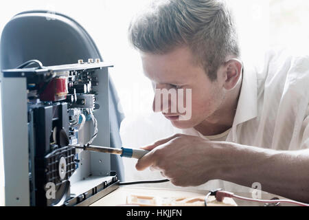 Engineer repairing CD player in workshop, Freiburg Im Breisgau, Baden-Württemberg, Germany - Stock Photo