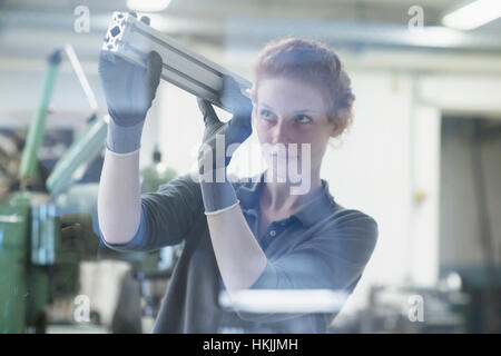 Young female engineer looking at machine part in an industrial plant, Freiburg im Breisgau, Baden-Württemberg, Germany - Stock Photo