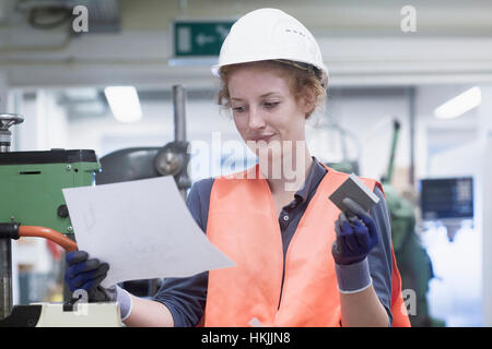 Young female engineer holding machine part with paper in an industrial plant, Freiburg im Breisgau, Baden-Württemberg, - Stock Photo