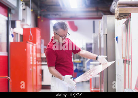 Male engineer examining circuit board in industry,Hanover,Lower Saxony,Germany - Stock Photo