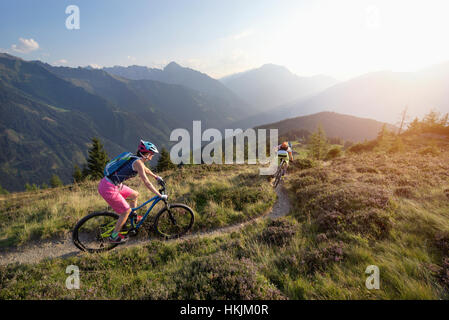 Two mountain bikers riding on hill in alpine landscape, Zillertal, Tyrol, Austria - Stock Photo