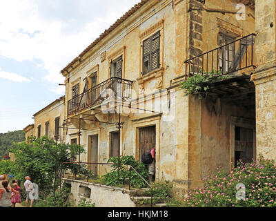 Tourists and ruined buildings left abandoned after the 1953 earthquake in village of Assos on Greek island of Kefalonia - Stock Photo