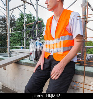 Home repair, building restructuring. Construction worker, with reflective orange jacket, on a terrace - roof for - Stock Photo
