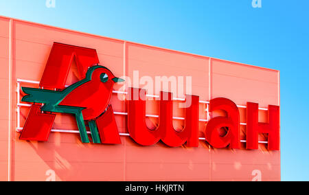 Auchan trade mark over blue sky background. French distribution network Auchan united more than 1300 shops - Stock Photo
