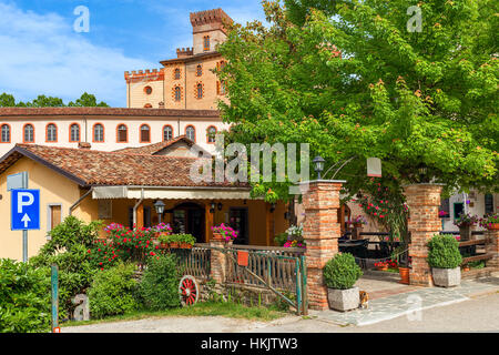 Small outdoor restaurant and old medieval castle on background in town of Barolo, Piedmont, Northern Italy. - Stock Photo