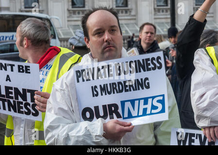 London, UK. 28th January, 2017. A man in a white suit holds a poster 'Private Business is Murdering OUr NHS' at - Stock Photo
