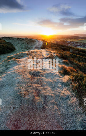 Sunrise over Moel-y-Gaer hill fort and frozen path with its commanding view over Flintshire towards Cheshire in - Stock Photo