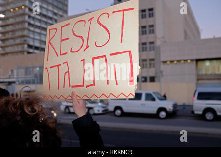 An Israeli woman holding a cardboard sign in English and Hebrew which reads 'Resist' during a demonstration against - Stock Photo