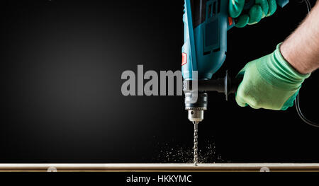 Man in Gloves Drilling wooden plank by Green Drill, close-up. Copy space. - Stock Photo