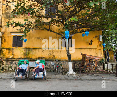 Cyclo drivers relaxing in the picturesque old town of Hoi An, Vietnam - Stock Photo