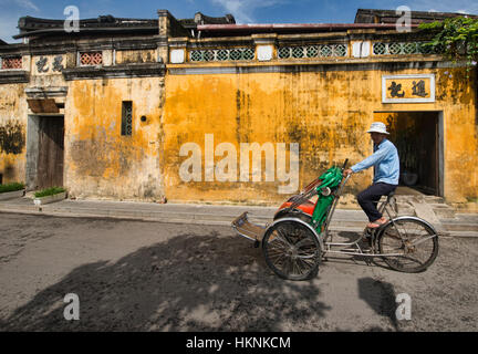 Cyclo driver and yellow walls in the picturesque old town of Hoi An, Vietnam - Stock Photo