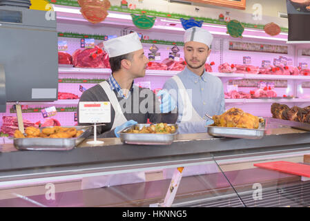 butchers standing behind counter in a supermarket - Stock Photo
