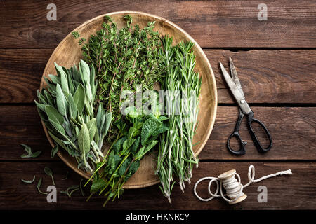 various fresh herbs, rosemary, thyme, mint and sage on wooden background - Stock Photo