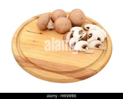 Sliced and whole fresh chestnut mushrooms with copy space on a wooden cutting board, isolated on a white background - Stock Photo