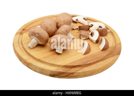 Whole and sliced chestnut mushrooms arranged on a wooden cutting board, isolated on a white background - Stock Photo