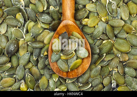 Organic pumpkin seeds in a wooden spoon. - Stock Photo