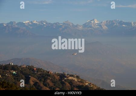View of the Everest mountain range from Nagarkot at sunrise as a tourist plane flies back from the popular Everest - Stock Photo