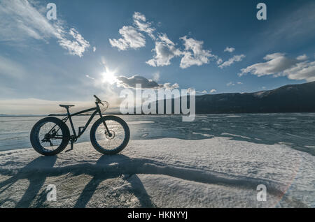Fatbike also called fat bike or fat-tire bike - Cycling on large tire wheels. Cyclist goes to his bike on the frozen - Stock Photo