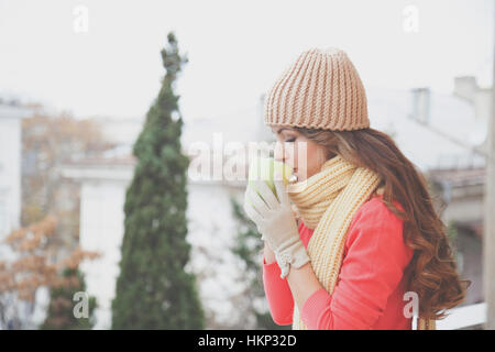 beautiful girl in a hat and gloves, drinking hot tea - Stock Photo