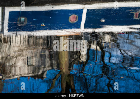 Boat, trees, birds are reflecting over Regent's Canal while people walks quietly along the river side. - Stock Photo