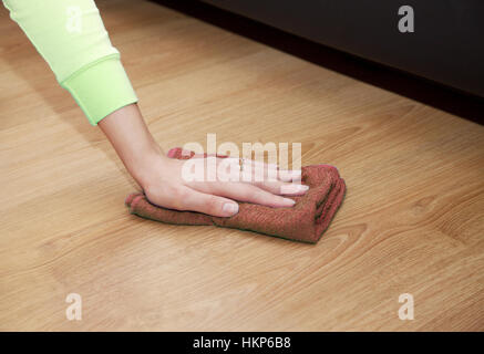 woman's hand cleaning the wooden floor with a brown floorcloth closeup - Stock Photo