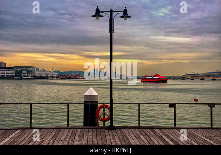 A lamp post on a wooden deck near the Pearl river as the Macao hong kong ferry arrives in Macau China. - Stock Photo