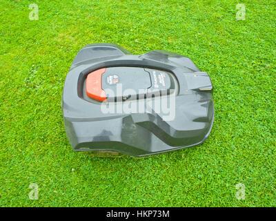 Husqvarna automower cutting lawn - Stock Photo