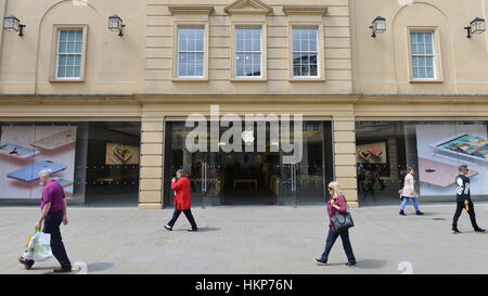 Bath, UK - May 13, 2016: People pass an Apple store on a city centre shopping street. - Stock Photo