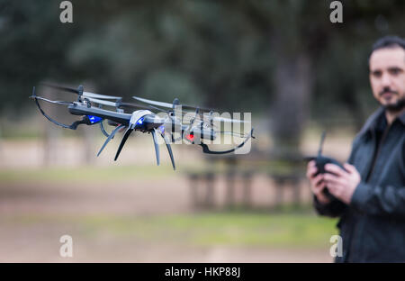 A man Operating The Drone By Remote Control In The Park - Stock Photo