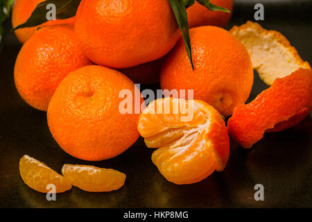 Several fresh juicy clementine tropical fruit on black plate. - Stock Photo