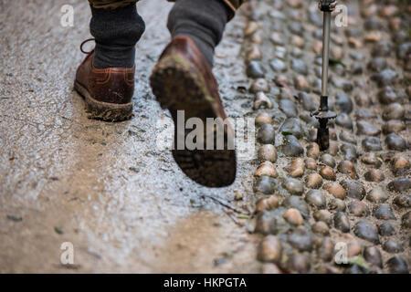 Senior walking along a path in Cornwall - Stock Photo