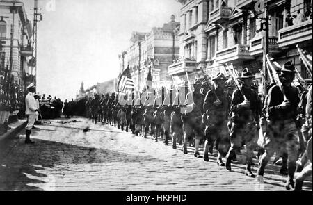 RUSSIAN CIVIL WAR 1918.  US troops  parade past  Japanese Marines standing to attention outside the Allied Headquarters - Stock Photo
