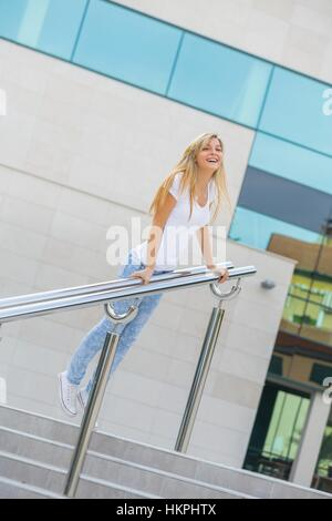 Healthy teen-girl blonde inclined on metal fence eyes-contact smiling smile happy happiness giggling giggle MR - Stock Photo