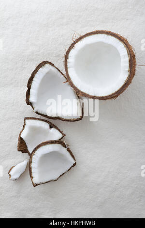 Pieces of a whole coconut cracked open on a white background - Stock Photo