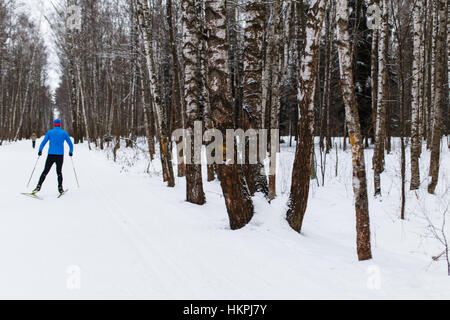 Man skiing on snowy road - Stock Photo