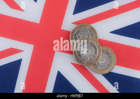 Three UK £2 coins on a Union Jack - metaphor for post-Brexit / British economy.