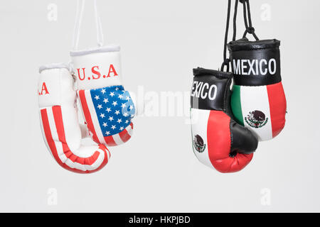 America-Mexico stand-off (Donald Trump) represented by hanging USA and Mexican emblem boxing gloves. NAFTA breakdown - Stock Photo