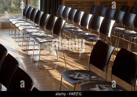 Strong window light plays on chairs set up in a hall for a conference. - Stock Photo