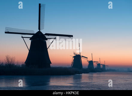 Winter sunrise over the windmills at the Kinderdijk UNESCO World Heritage Site in the Netherlands - Stock Photo